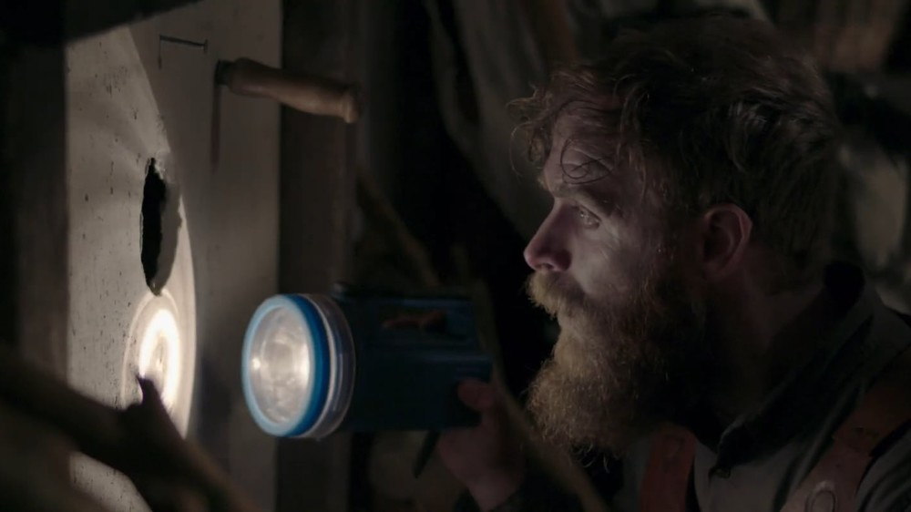 A bearded man holds a flashlight near a small hole in a wall in Caveat